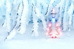 Beautiful christmas tree in a snowy park. A metal candlestick in the form of a New Year`s spruce. New Year`s art image in blue to. Nes. In the woods the snow royalty free stock image