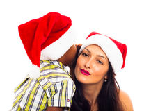 Beautiful Christmas woman and boy whispering. Beautiful young women and child boy in Christmas hat whispering, isolated on white background Royalty Free Stock Photography