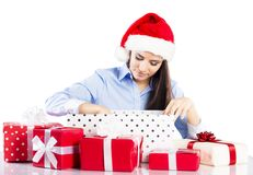 Beautiful christmas woman. Beautiful woman with christmas hat has gifts on desk in her office Royalty Free Stock Images