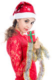 Beautiful christmas woman is holding red gift in studio. Royalty Free Stock Photo