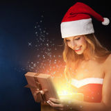 Beautiful christmas woman open fairy gift. On dark background Stock Photography