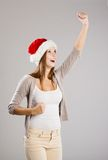 Beautiful christmas woman. Portrait of attractive woman isolated on gray, studio shot in christmas hat Stock Photo