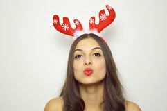 Beautiful christmas woman send a kiss at camera with reindeer horns on her head, gray background Royalty Free Stock Images