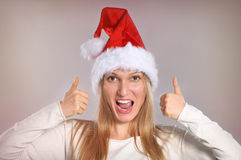 Beautiful Christmas woman with thumbs up sign. Smiling girl with Santa hat Royalty Free Stock Photo