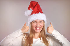 Beautiful Christmas woman with thumbs up sign. Smiling girl with Santa hat Stock Images