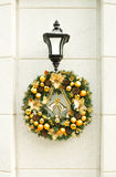 Christmas wreath on lantern on white wall. Royalty Free Stock Image