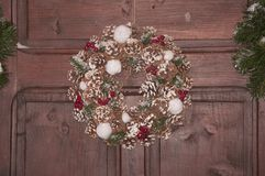 Beautiful Christmas wreath with green conifer, cones and berries. New Year decoration on brown background stock image