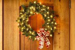 Beautiful Christmas wreath home decorations lights on front door of house stock images