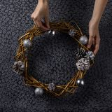 Beautiful Christmas wreath painted in gold in the hands of a woman. The concept of preparing for the holidays. Festive interior.Square stock photos