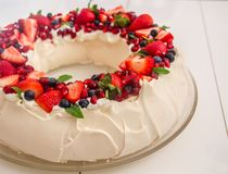 Beautiful Christmas wreath shaped Pavlova cake made of french meringue, whipped cream, decorated with fresh berries. Beautiful Christmas wreath shaped Pavlova royalty free stock photo