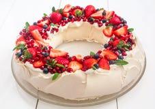 Beautiful Christmas wreath shaped Pavlova cake made of french meringue, whipped cream, decorated with fresh berries. Beautiful Christmas wreath shaped Pavlova royalty free stock photography