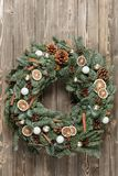 Beautiful Christmas wreath on wooden boards. Preparation for holidays concept. Flower shop is a master work of a Stock Photo