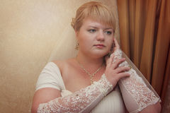 Beautiful chubby bride. Lovely chubby bride posing near curtain Stock Image