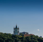 Beautiful church on a mountain with trees against a blue sky bac Stock Images