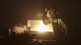 Beautiful cinematic hammer blows on the anvil. Blacksmith hits the workpiece on the anvil