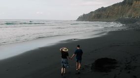 Beautiful cinematic shot. A young couple walks and then runs by the arm along a black volcanic sand beach. Aerial view