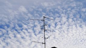TV Television aerial antenna majestic cirrocumulus clouds. Beautiful cirrocumulus clouds on a summer afternoon with TV Television aerial antenna in the middle of stock footage