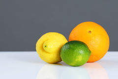 Beautiful citrus fruits in front of grey. Beautiful studio still life of whole citrus fruits, orange, lemon and lime on white table and grey wall, perfect Royalty Free Stock Image