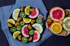 Beautiful citrus orange grapefruit Mandarin sweetie kiwi fruit quince cut pieces of a slice the slices in a large plate black and royalty free stock photography