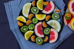Beautiful citrus orange grapefruit Mandarin sweetie kiwi fruit quince cut pieces of a slice the slices in a large plate black and stock image