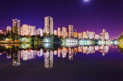 Beautiful city lights reflected on the water of the lake at nig. Landscape of the city, buildings, the lake Lago Igapo and the city lights. Beautiful city lights Royalty Free Stock Images