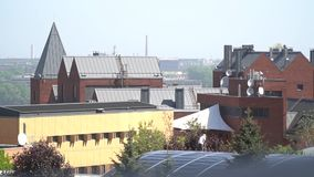 A view of the city and a man watering trees in the courtyard. A beautiful city with red brick buildings and high roofs stock video footage