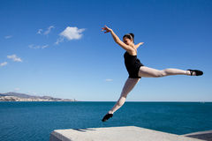 Beautiful classic dancer jumping over a big stone block. Royalty Free Stock Photos