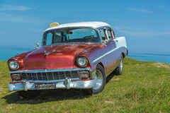 Beautiful classic retro car parked on green cliff Royalty Free Stock Photography