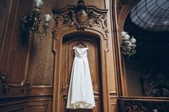 Beautiful classic silk dress hanging on old wooden wall in room. Morning preparation. gown shopping Stock Images