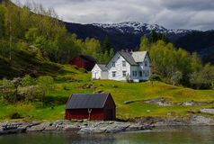 Beautiful, classic white farmhouse next to fjord in Norway. A classic white farmhouse with red outbuildings next to a fjord in Norway.  A mountain range with Stock Photography