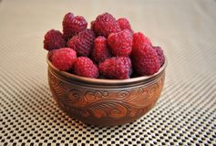 Beautiful clay dish with raspberries on a napkin. stock images