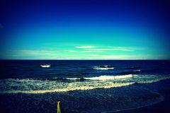 Beautiful clean coast of the endless blue sea towards the bright sun Stock Photography