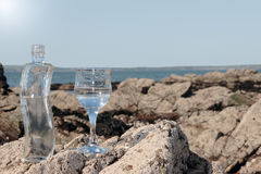 Beautiful clean environment. Single bottle and a glass of pure natural water standing on the rocks on a beach in ireland showing a clean environment Stock Photos
