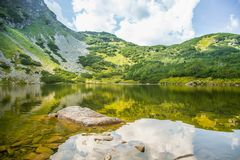 A beautiful, clean lake in the mountain valley in calm, sunny day. Mountain landscape with water in summer. Tatry mountains in Slovakia, Europe royalty free stock photos