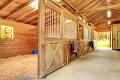 Beautiful clean stable barn. Stable barn with beam ceiling and open door to a clean stall Royalty Free Stock Image
