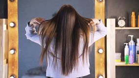 Beautiful clean well-groomed hair of a young woman after a Botox procedure in a beauty salon. The girl is happy with the