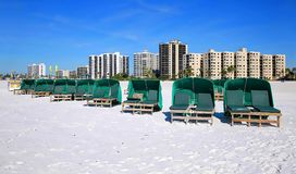 Beautiful clear blue skies on Fort Myers Beach, Florida, USA. Green cabanas ready to be rented in front of Fort Myers Beach hotels and time share condos Stock Image