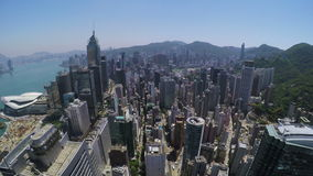 Beautiful Clear Sky Hong Kong City Aerial. 4K Aerial view of Wanchai and Hong Kong East of Hong Kong. Wide aerial backward shot flying over office buildings and stock video footage