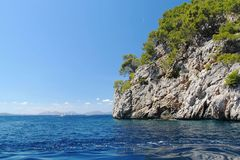 Beautiful cliff in Mediterranean sea covered with green trees. Blue sky background. Spain royalty free stock photos