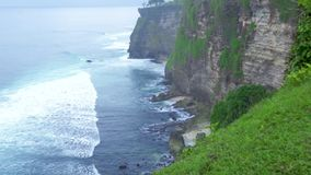 Beautiful cliff on ocean shore and water waves on skyline landscape. High cliff mountain covered tropical plants and. Trees on splashing sea waves background stock video footage