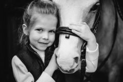 Beautiful close portrait Girl sit beiside horse on bridge. forest on background. black and white. black and white royalty free stock photo