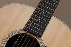 Beautiful close up abstract picture of a classical acoustic guitar with soft light brown beige natural wood grain, ebony fretboard Royalty Free Stock Image