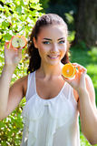 Beautiful close-up portrait of young woman with orange and apple Stock Photography
