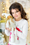 Beautiful close up portraite of curly girl with gold Christmas garlands magic lights and tree decorations hugs toy angel Stock Image