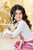 Beautiful close up portraite of curly girl with gold Christmas garlands magic lights and tree decorations hugs toy deer Stock Photos