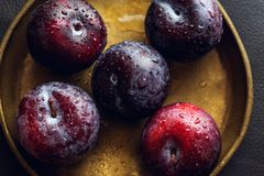 Plums on a plate, top view stock images