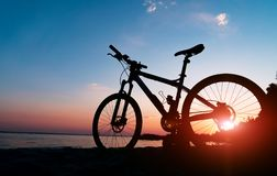 Beautiful close up scene of bicycle at sunset, sun on blue sky with vintage colors, silhouette of bike forward to sun.  stock photos