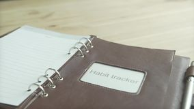 Beautiful close up shot of light brown leather habit tracker journal note pad book silver pen holder on wooden table. Beautiful close up shot of light brown stock video