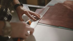 Beautiful close-up shot of female hands cutting big leather piece on light workshop table with knife and curve ruler. Beautiful close-up shot of skilled female stock video footage