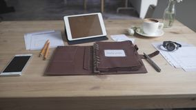 Beautiful close up view on business work area desktop with tablet cell phone coffee mug watch leather note book. Pad stock video